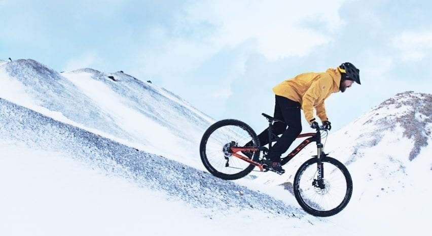 A man on a mountain bike going down a snowy hill