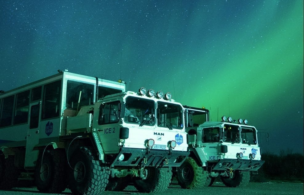Glacier jeeps parked under the clear Northern lights sky